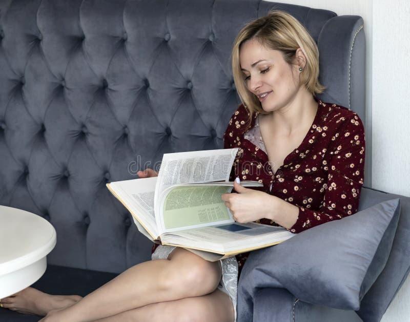Kvinna p? soffan i rummet royaltyfria foton