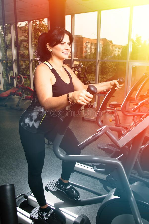 Kvinna plus format i idrottshallen som gör övningar med rinnande utbildande app arkivfoton