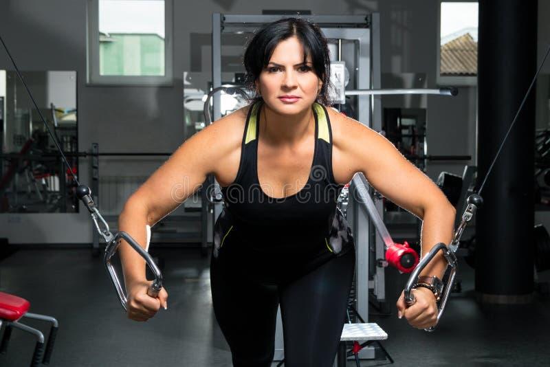 Kvinna plus format i idrottshallen som gör övningar med utbildningsapparaturen, royaltyfri bild