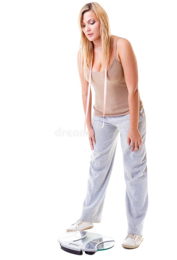 Kvinna plus formatet med skalan, viktkontroll arkivfoto