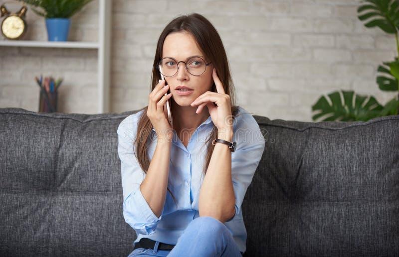 kvinna pratar på smartphone hemma arkivfoto