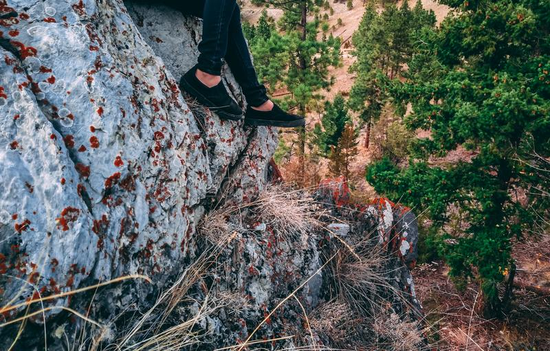 Kvinna` s lägger benen på ryggen att dingla från vaggar klippan royaltyfri fotografi