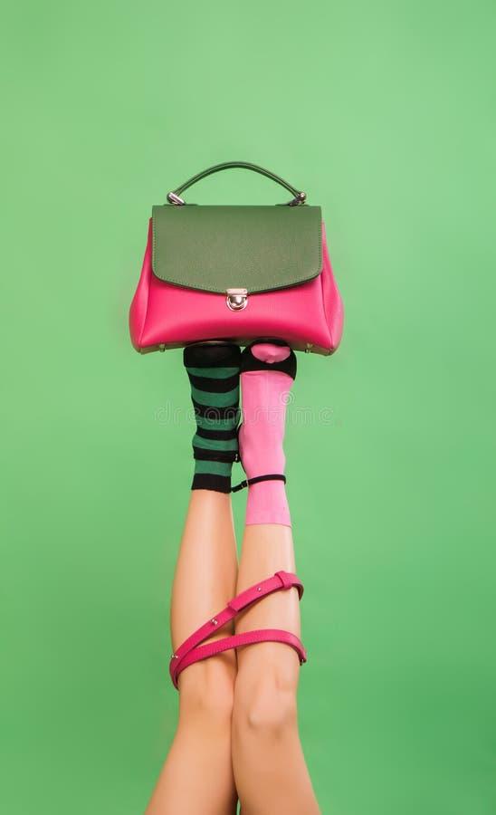 Kvinna` s lägger benen på ryggen den hållande handväskan på en grön bakgrund fotografering för bildbyråer