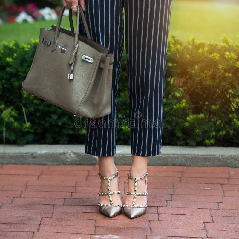 Kvinna` s lägger benen på ryggen i gråa skor för höga häl Ljusa grå färgskor, påse och blåttflåsanden Bomull flåsar, stilfulla da royaltyfri bild