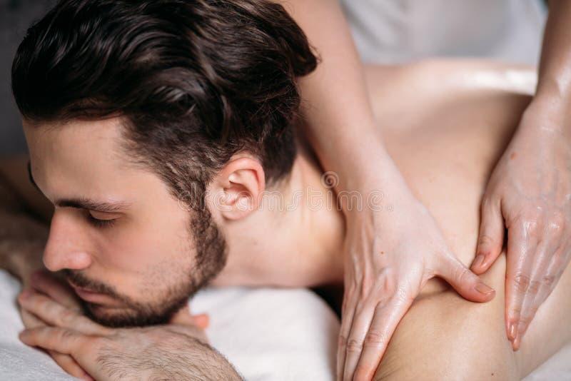 Kvinna` s räcker att göra massage till den stiliga orakade mannen fotografering för bildbyråer