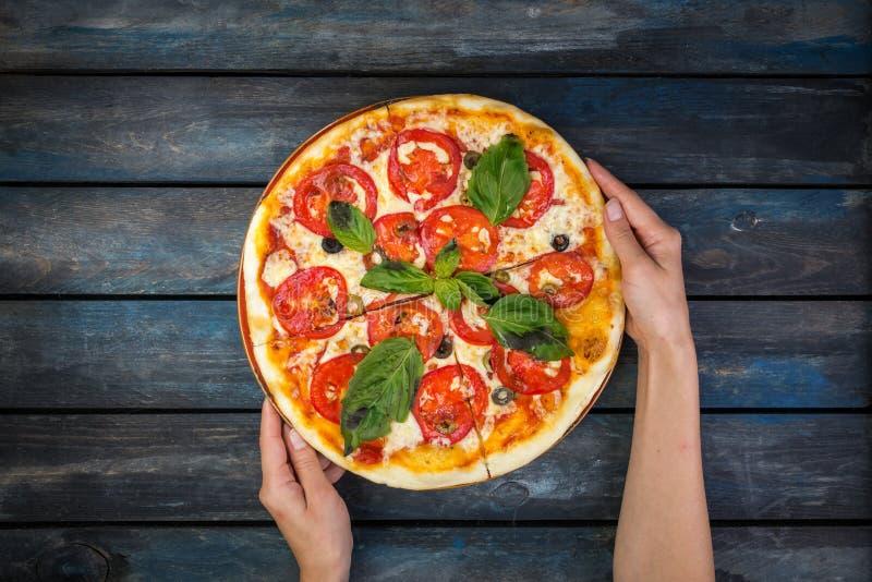 Kvinna` s räcker att rymma en perfekt pizzamargarita med tomatskivor, oliv och basilikasidor Top beskådar arkivfoton