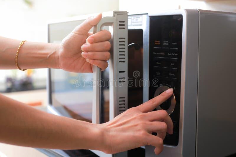Kvinna` s räcker bokslutmikrovågen Oven Door And Preparing Food in royaltyfria bilder
