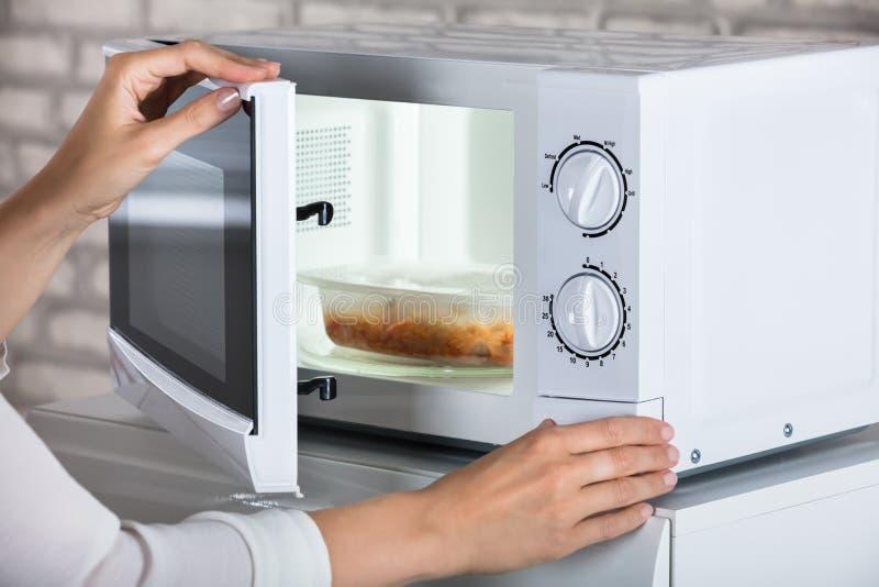 Kvinna` s räcker bokslutmikrovågen Oven Door And Preparing Food royaltyfri foto