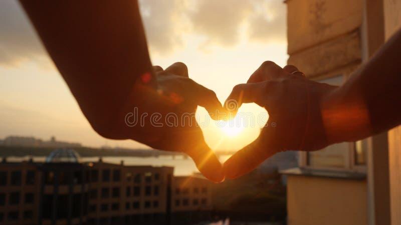 Kvinna` s räcker framställning av en hjärta till och med solen på den fantastiska solnedgången på härlig stads- stadsbakgrund med arkivbilder