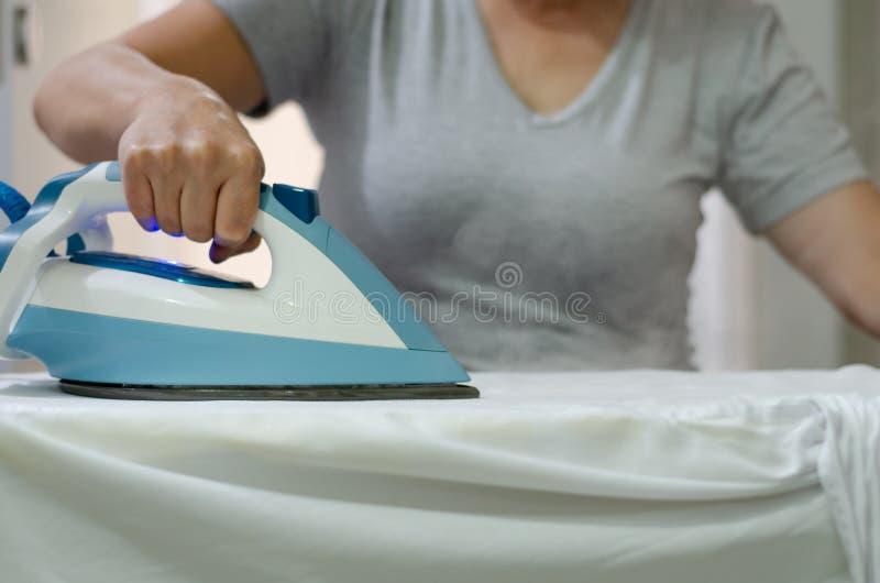 Kvinna` s räcker hållande varmt järn som ångar kläder, nollan för grunt djup royaltyfria foton