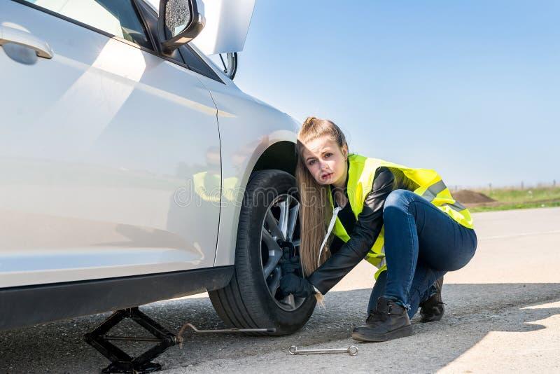 Kvinna som ändrar det skadade hjulet och fixar det royaltyfria foton