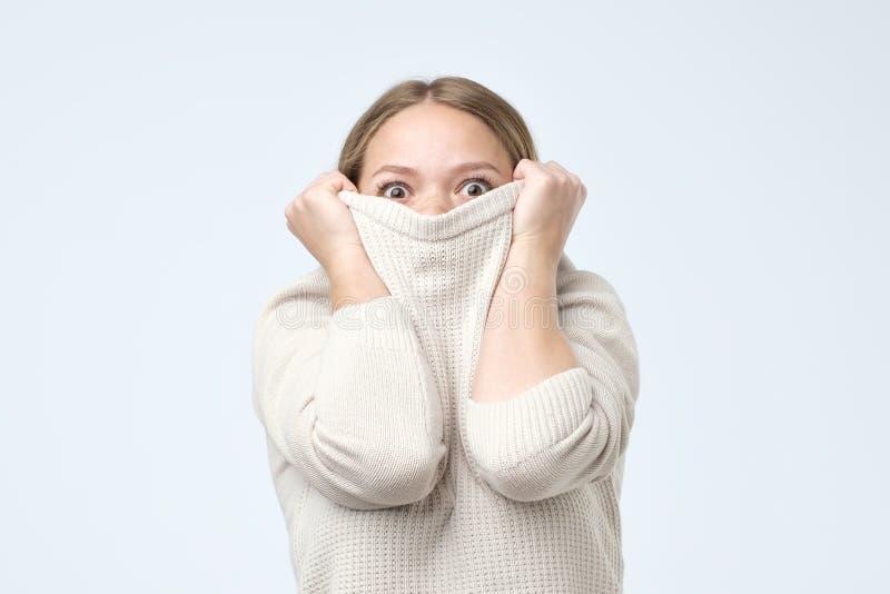 Kvinna som är barnsligt försvinna i hennes kläder som ser från under Hon skrämmas med examenresultat arkivbild