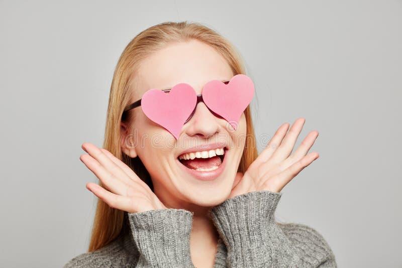 Kvinna som är förälskad med två rosa hjärtor på hennes ögon arkivbilder