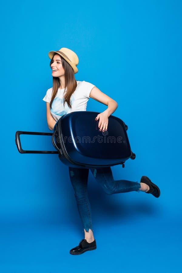 Kvinna som är klar för sommarloppet som isoleras på blå bakgrund Nätt kvinnaspring med bagage på blå bakgrund royaltyfri fotografi
