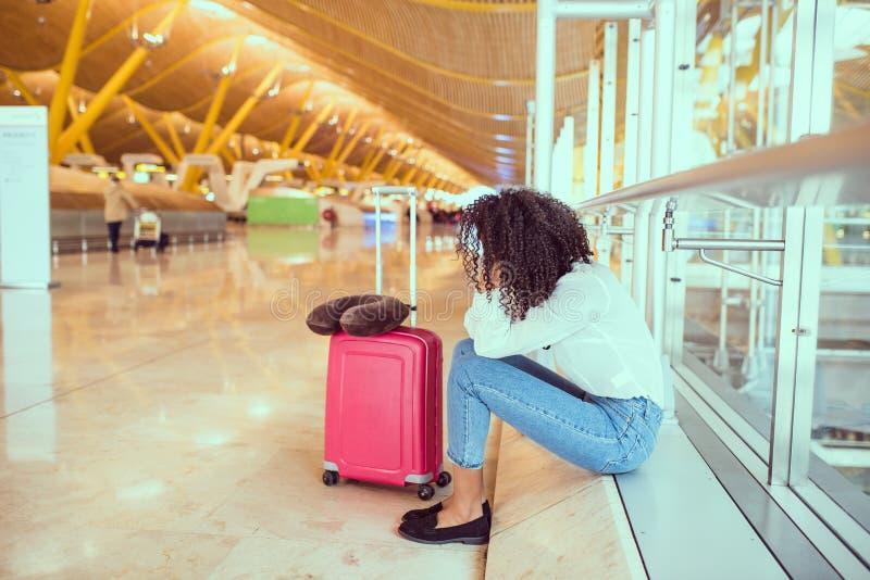 Kvinna som är ledsen och som är olycklig på flygplatsen med det avbrutna flyget royaltyfria bilder