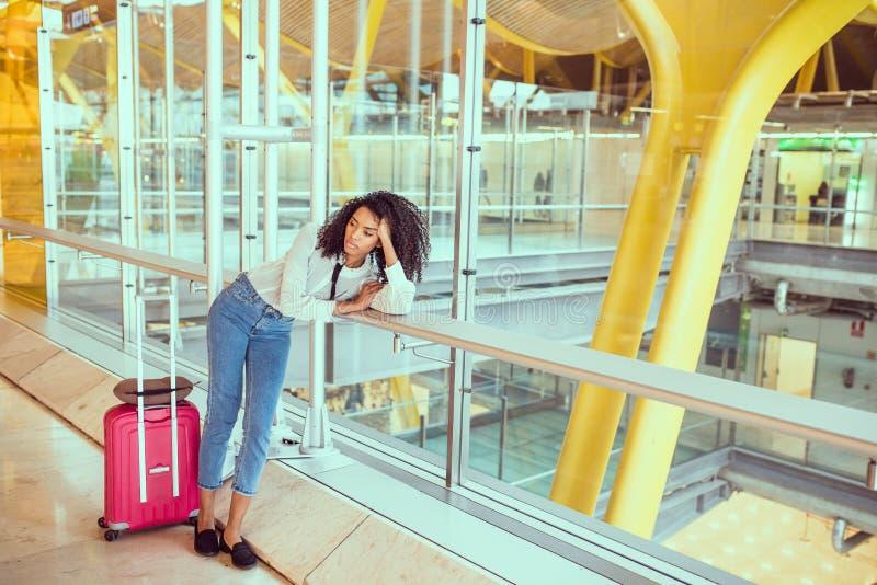 Kvinna som är ledsen och som är olycklig på flygplatsen med det avbrutna flyget arkivfoto