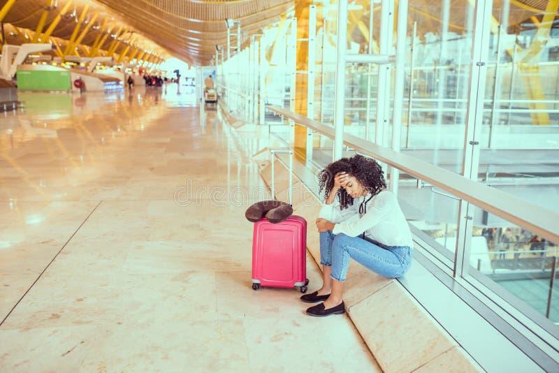 Kvinna som är ledsen och som är olycklig på flygplatsen med det avbrutna flyget royaltyfri foto