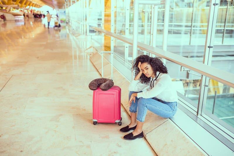 Kvinna som är ledsen och som är olycklig på flygplatsen med det avbrutna flyget arkivbild