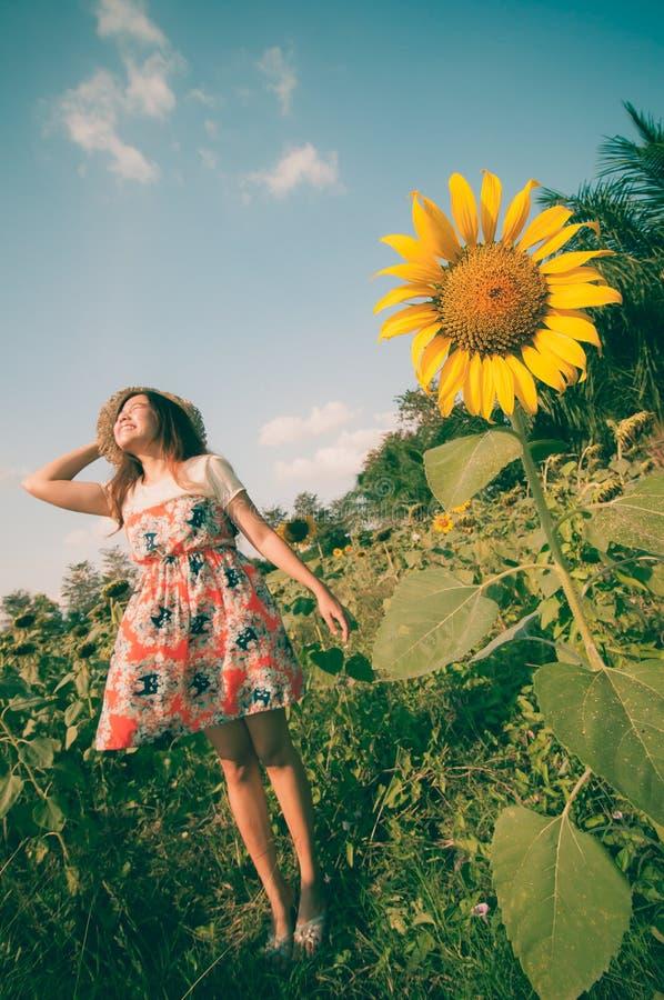 Kvinna som är lycklig i solrosblommafält royaltyfri fotografi
