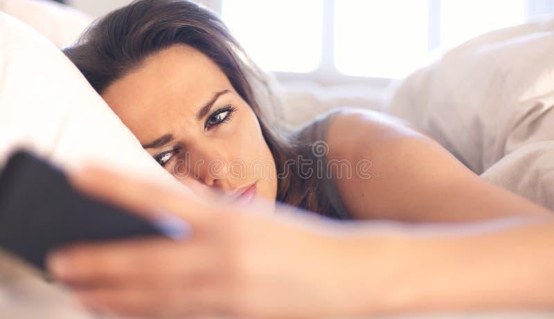 Kvinna som är olycklig med ett textmeddelande arkivbilder