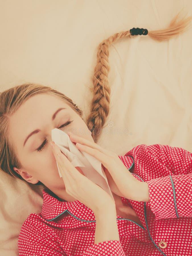 Kvinna som är sjuk ha influensa som ligger på säng arkivfoton