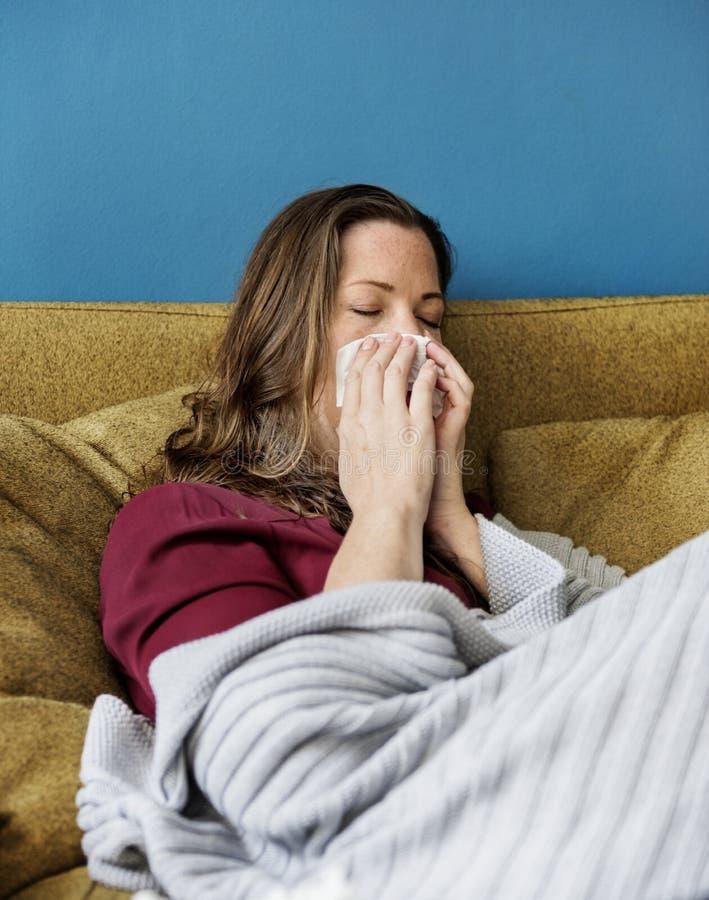 Kvinna som är sjuk på soffan arkivbilder