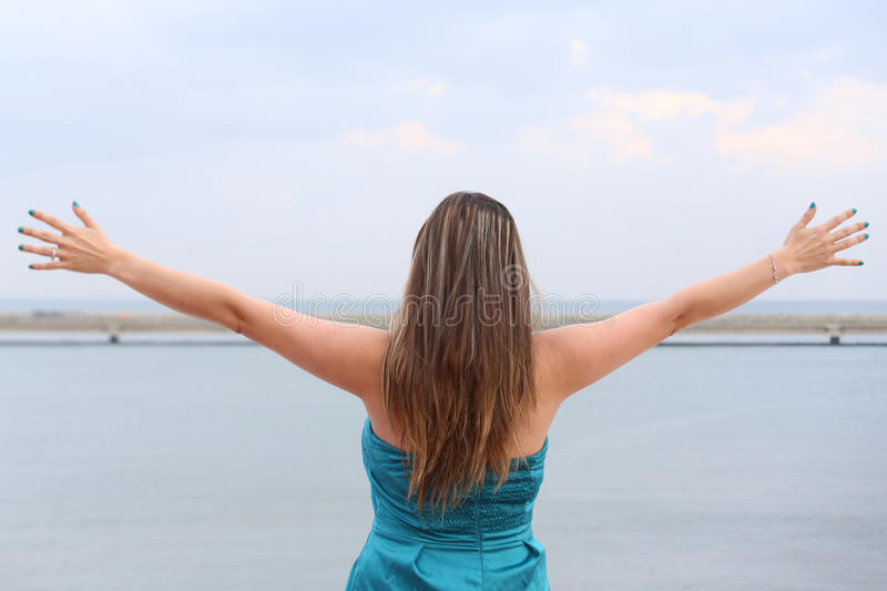 Kvinna som är stående tillbaka med öppna armar arkivbilder