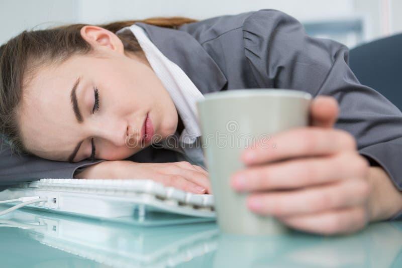 Kvinna som är stupad sovande på skrivbordet arkivbild