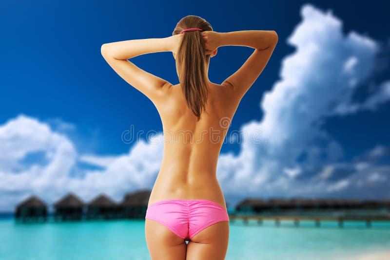 Kvinna som är topless på den härliga stranden med vattenbungalower arkivfoto