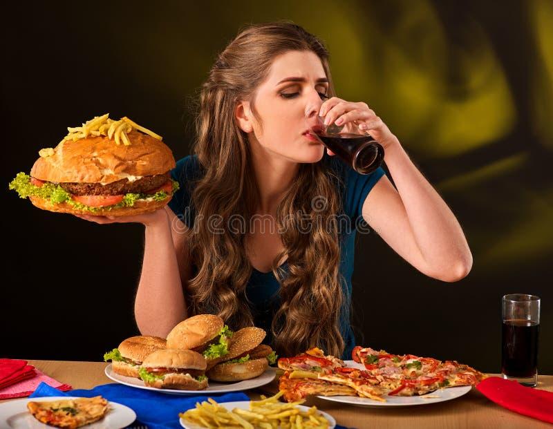 Kvinna som äter den fransmansmåfiskar och hamburgaren på tabellen royaltyfria bilder