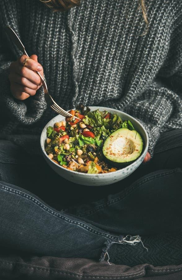 Kvinna som äter den nya sallad, avokadot, bönor och grönsaker från bunken royaltyfria foton