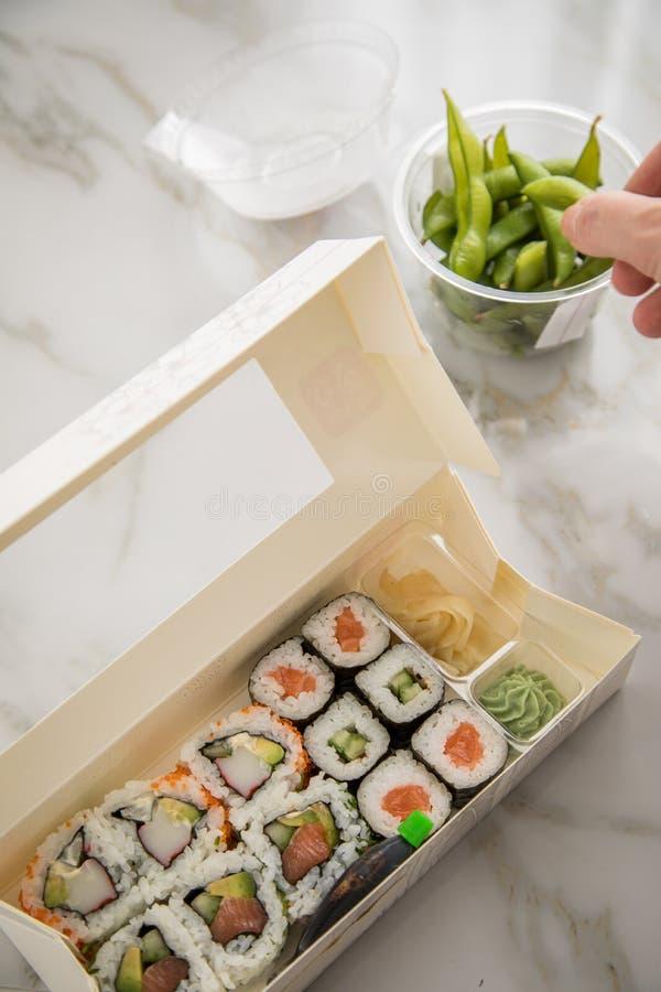 Kvinna som äter edamame, lax, surimi, gurka och avokado Maki och insida - ut Kalifornien sushi med soya, inlagd ingefära, arkivfoton