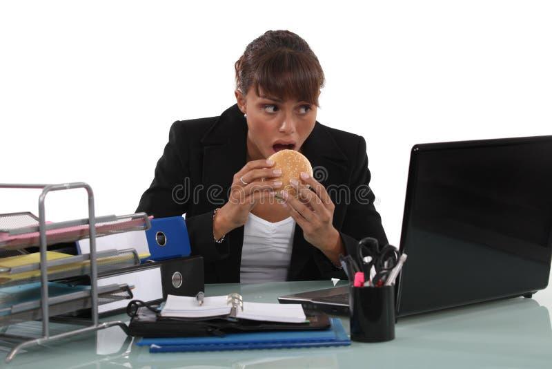 Kvinna som äter en hamburgare royaltyfria foton