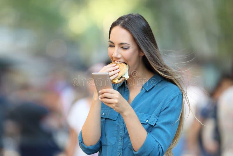 Kvinna som äter en hamburgare som rymmer en smart telefon royaltyfri bild