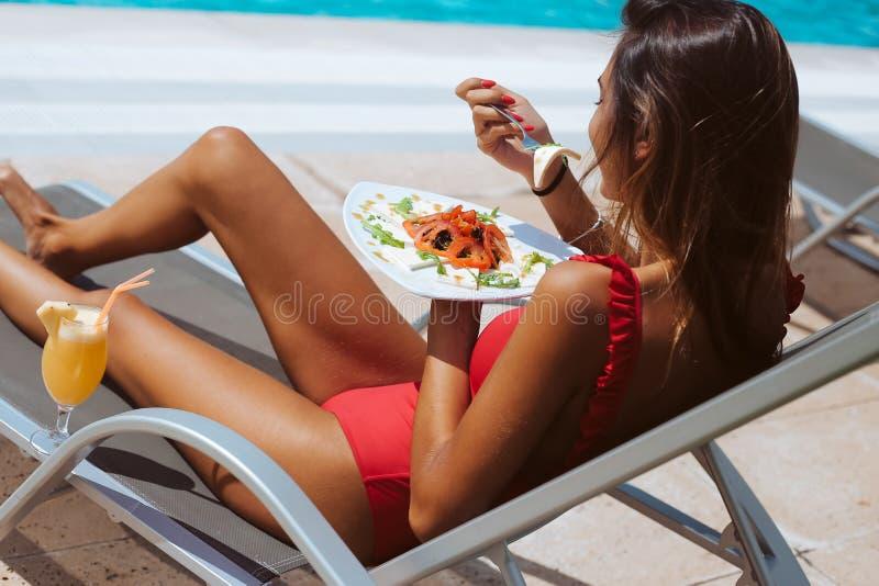 Kvinna som äter en ny sallad och dricker fruktsaft royaltyfria foton
