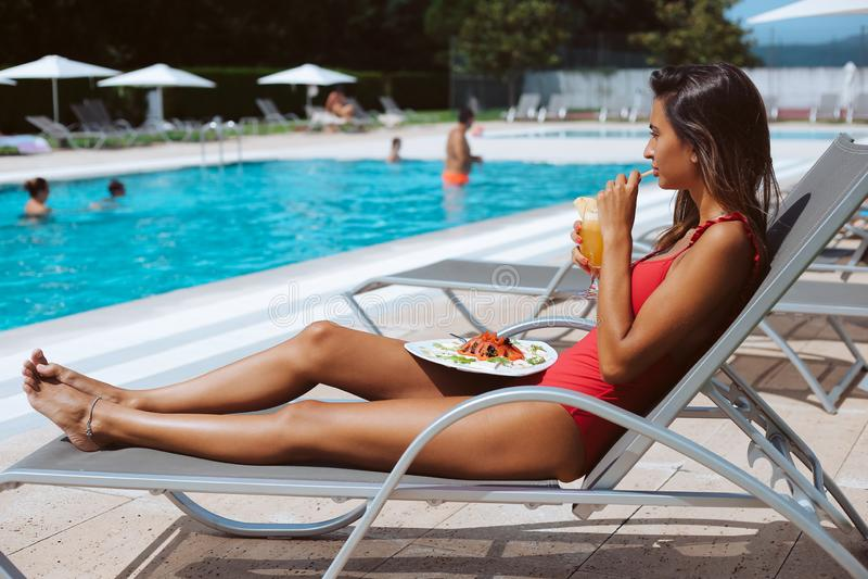 Kvinna som äter en ny sallad och dricker fruktsaft arkivfoto