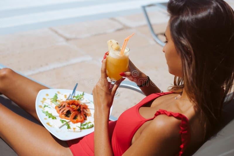 Kvinna som äter en ny sallad och dricker fruktsaft royaltyfri fotografi