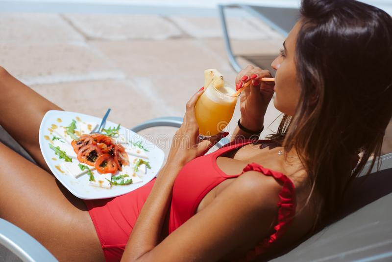 Kvinna som äter en ny sallad och dricker fruktsaft royaltyfri foto