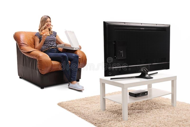 Kvinna som äter en skiva av pizza och håller ögonen på TV royaltyfri bild