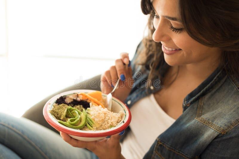 Kvinna som äter en strikt vegetarianbunke fotografering för bildbyråer
