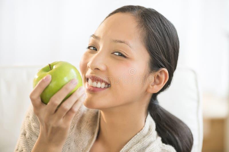 Kvinna som äter farmodern Smith Apple On Sofa royaltyfria foton