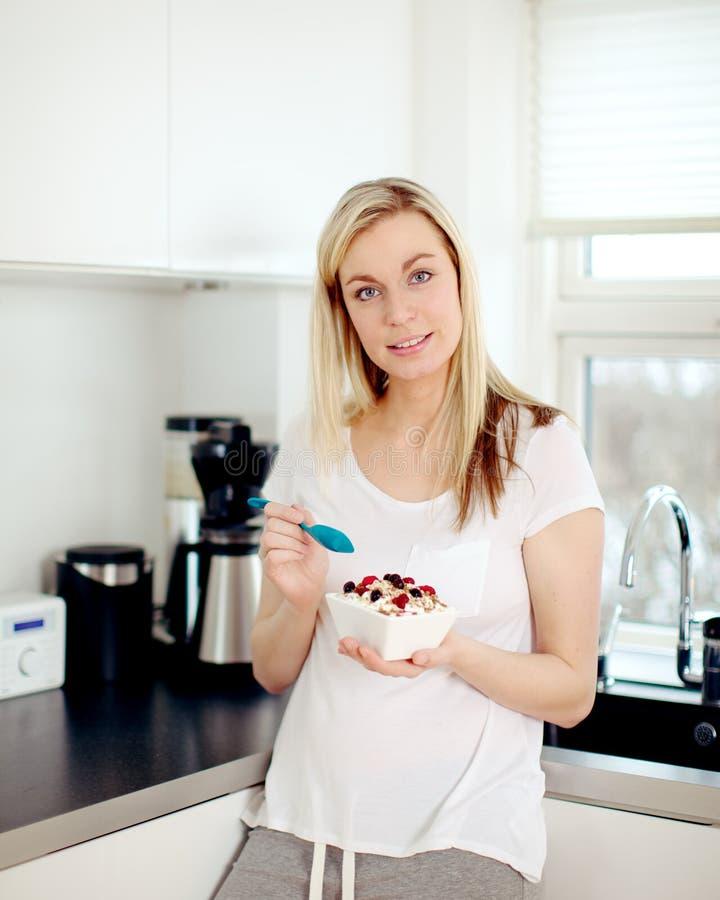 Kvinna som äter frukosten i kök arkivfoton