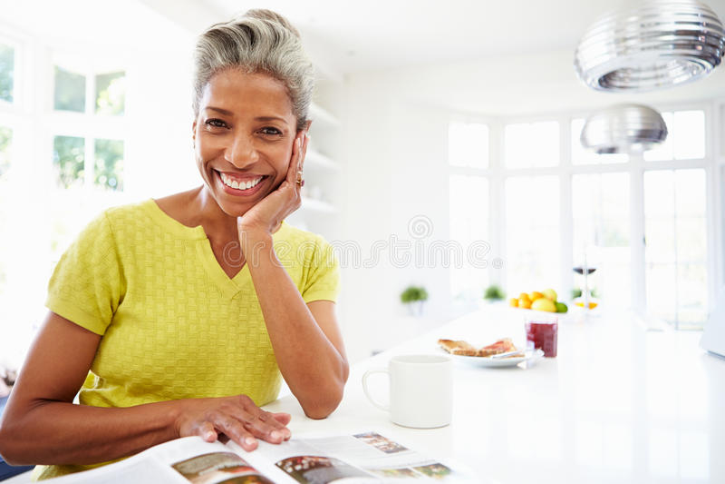 Kvinna som äter frukosten och den läs- tidskriften royaltyfri bild