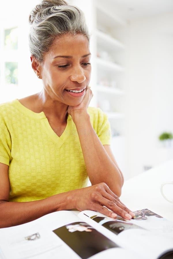 Kvinna som äter frukosten och den läs- tidskriften royaltyfria bilder