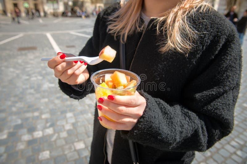 Kvinna som äter fruktsallad från lunchasken i staden arkivbild