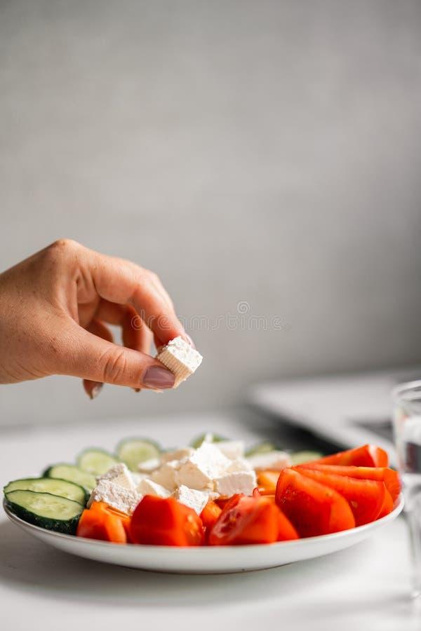 Kvinna som äter grönsaker och dricksvatten på arbete arkivfoton