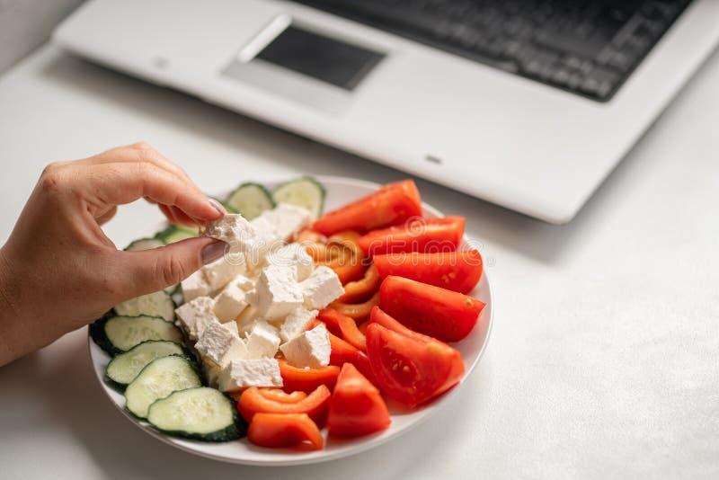 Kvinna som äter grönsaker och dricksvatten på arbete royaltyfri bild