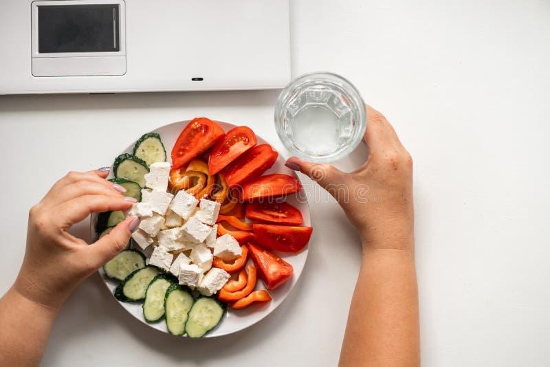 Kvinna som äter grönsaker och dricksvatten på arbete royaltyfria bilder