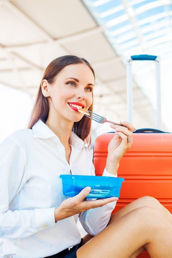 Kvinna som äter hemlagad mat från den plast- behållaren på flygplatsen royaltyfria bilder