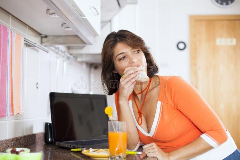Kvinna som äter hennes frukost arkivfoton
